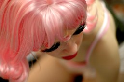 With her makeup, including feathered fake eyelashes, done and her costume almost finished, Baker adjusts her blond wig in the mirror to transform into Barbie. She completed the outfit with a pink short-sleeved collared shirt, which she attached Velcro to so that McGinnis could remove it easily during the performance. (Eugene OR, 2007)