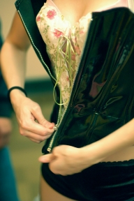 "Baker zips up a black bustier over her white corset in preparation for another one of her performances. Besides choreographing and performing in ""Barbie Girl,"" Baker also choreographed and performed in ""Boom, Boom, Boom,"" and ""Coin Operated Boy,"" the first and second amateur acts of the night. (Eugene OR, 2007)"